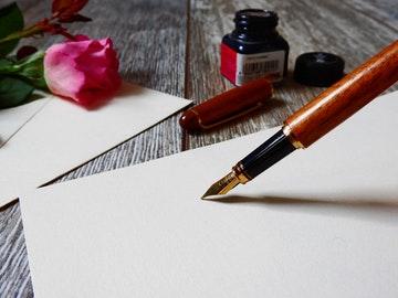 Imagen de una mesa con un folio en blanco y una pluma a punto de escribir unas frases motivadoras célebres