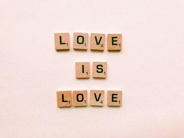 Foto en la que ve escrito love es love con fichas que usamos para representar la página de frases motivadoras de amor
