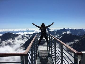 para ilustrar está página de Frases motivadoras de la vida, hemos usado esta foto de una chica subida a un mirador con los brazos abiertos en el que se ven las montañas