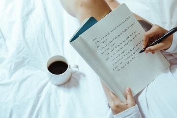 Chica en la cama con un cafe y escribiendo en una libreta frases motivadoras de trabajo
