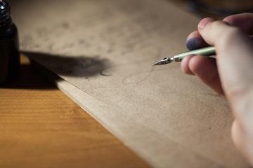Mano manchada de tinta escribiendo Frases motivadoras