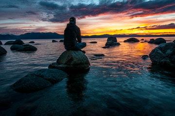 Joven sentado sobre una roca en el mar viendo el atardecer, imágen que usamos para representar nuestra página de frases para reflexionar