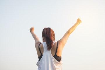 Chica con brazos estirados en alto después de leer frases motivadoras cortas