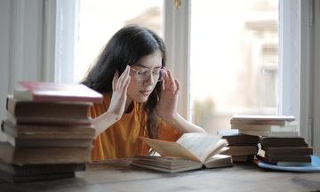 Chica sentada a la mesa delante de un libro  con los dedos en las sienes y los ojos cerrados, parece que intentara motivarse. Debería aprender frases motivadoras para estudiantes.