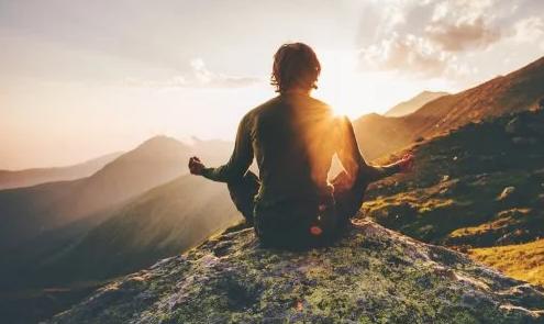 Hombre aprendiendo como relajarte en dentado en una montaña viendo puesta de sol