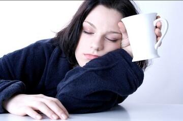 Chica con apatía sentada a la mesa medio tumbada y con ojos cerrados