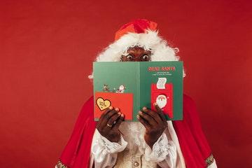 Papá Noel leyendo un libro de frases de navidad